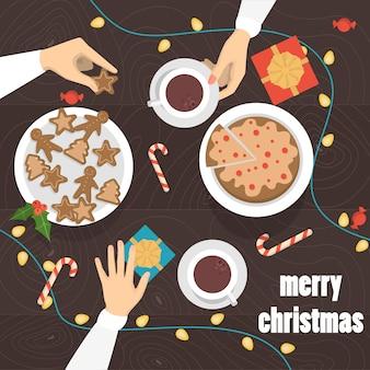 クリスマステーブルトップビューでジンジャーブレッドとお茶とコーヒーを飲む人。テーブルの上のプレゼントやお菓子。図