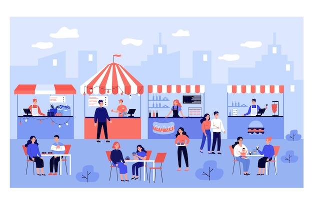 Люди едят в уличном фуд-корте, посещая фестиваль в парке