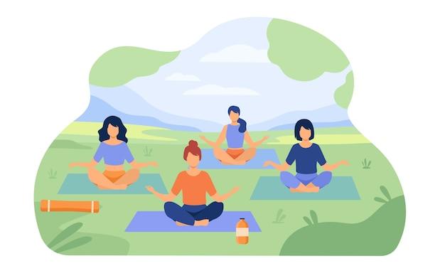 公園で野外ヨガ教室を楽しんでいる人。蓮華座の草の上に座っている女性。