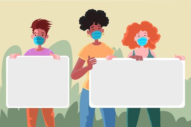 Persone in maschere facciali con cartelli