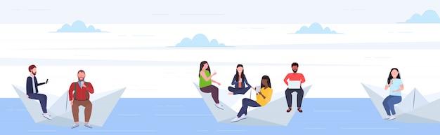 Люди, плавающие на бумажной лодке, смешанные расы, мужчины, женщины, использующие гаджеты, путешествующие вместе, цифровая зависимость.