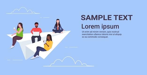 Люди, летающие на бумажном самолете, микс мужчины женщины, использующие гаджеты, путешествующие вместе цифровая зависимость веб-серфинг концепция горизонтальное копирование пространство