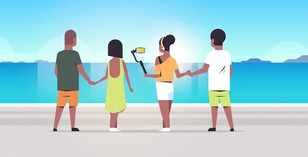 People group on beach using selfie stick taking photo smartphone camera summer vacation concept rear view   friends standing together seaside background full length horizontal