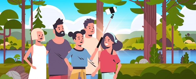 People group in forest using selfie stick taking photo on smartphone camera hiking concept friends standing together landscape background portrait horizontal