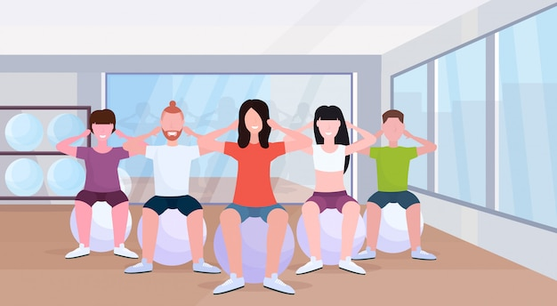 People group sitting on fitness ball men women doing press exercises training in gym aerobic workout healthy lifestyle concept modern health club studio interior horizontal