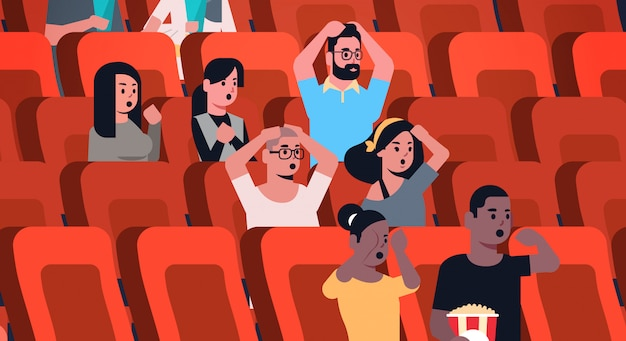 People group watching horror movie and screaming sitting in cinema with popcorn and cola mix race men women looking scared flat portrait horizontal