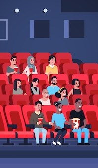 People group watching movie sitting in cinema with popcorn and cola mix race men women having fun laughing at new comedy flat full length vertical