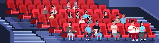 新しいコメディフラット全長水平で笑って楽しんでいるポップコーンとコーラのミックスレースの男性女性と映画に座って映画を見て人々のグループ
