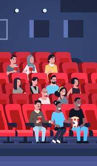 ポップコーンとコーラの映画館で座っている映画を見ている人々のグループは、新しいコメディフラット全長垂直で笑って楽しんでいるレースの男性女性