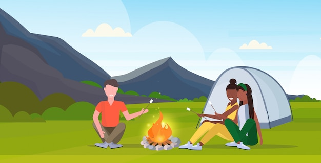 People hikers roasting marshmallow candies on campfire hiking camping concept mix race man women travelers on hike mountains nature landscape horizontal full length flat