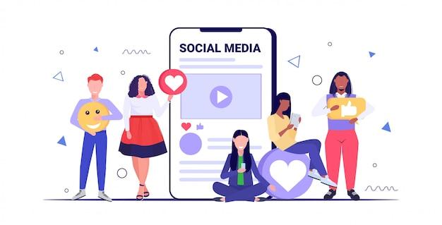 Люди, держащие социальные медиа иконки сети чат пузырь концепция коммуникации