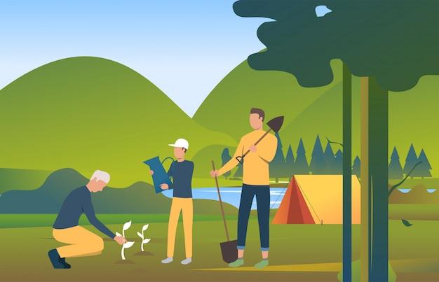 スペードを押しながら野生の自然の中で木を植える人々