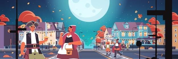 町を歩く衣装を着た人々は、幸せなハロウィーンのお祝いのコンセプトグリーティングカード水平ベクトルイラストをトリックまたは扱います