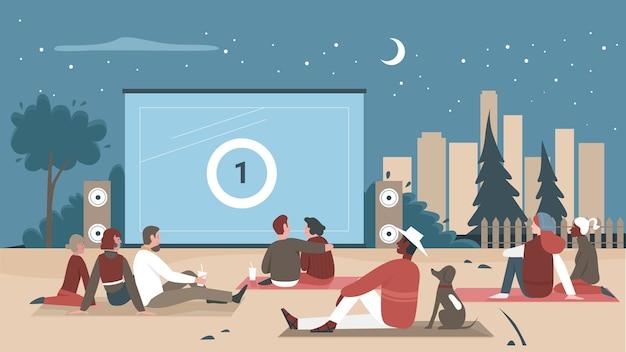 デジタル映画を見ている野外映画館の人々