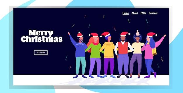 楽しいミックスレースを楽しんでいるサンタの帽子の人々メリークリスマスを抱きしめる男性女性新年あけましておめでとうございます冬休みのお祝い