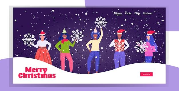 산타 모자에있는 사람들이 눈송이를 들고 메리 크리스마스 새해 복 많이 받으세요 겨울 휴가 축하 개념 믹스 레이스 남성 여성 함께 서있는 재미 방문 페이지