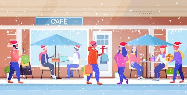 산타 모자를 걷는 사람들 야외 남성 여성 다채로운 쇼핑 가방을 들고 크리스마스 판매 겨울 휴가 개념 현대 도시 거리 건물 외관