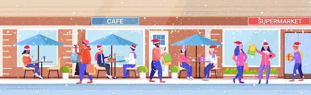 산타 모자를 걷는 사람들 야외 남성 여성 다채로운 쇼핑백 크리스마스 쇼핑 겨울 휴가 개념 현대 도시 거리 건물 외관