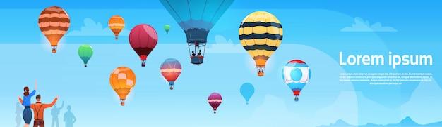 하늘 배너에 비행하는 다채로운 공기 풍선을보고하는 사람들