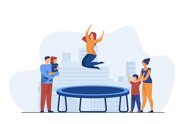 트램폴린에 점프하는 여자를 보는 사람들.
