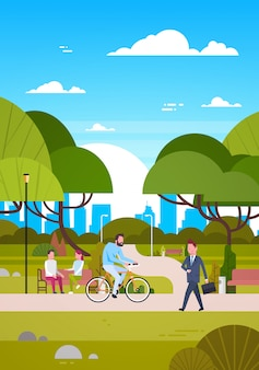 People outdoors in modern park sit on bench, walking and riding bicycle, human in nature communicating