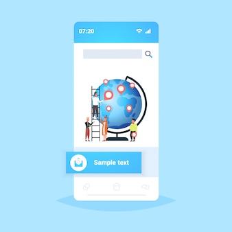 Люди, размещающие геотеги-указатели на глобусе путешественники около планеты земля с маркерами местоположения gps-навигация бизнес-позиция концепция путешествия экран смартфона мобильное приложение во всю длину