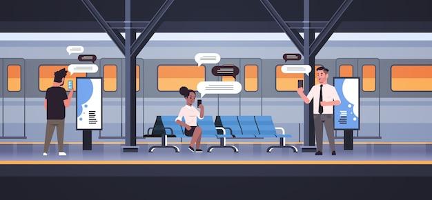 Платформа людей с помощью мобильного приложения в чате на смартфоне социальная сеть чат пузырь концепция связи поезд метро или железнодорожная станция полная длина горизонтальная векторная иллюстрация