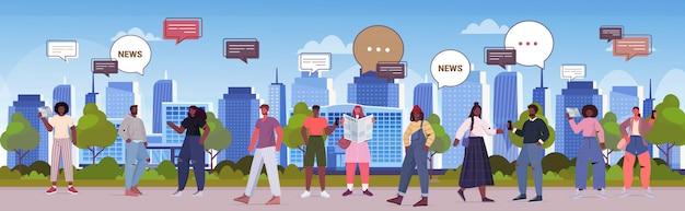新聞を読んで、毎日のニュースチャットバブル通信の概念を議論する人々。都市公園の完全な長さの水平方向の図を歩いて混血男性女性