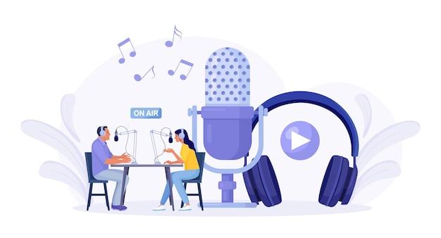 ラジオスタジオでポッドキャストを録音している人。ゲストにインタビューする女性ラジオホスト。ヘッドフォンで話している男性と女性。マスメディア放送。録音機器、マイク、ヘッドセット