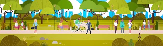 People relaxing in beautiful urban park walking riding bicycle and communicating horizontal