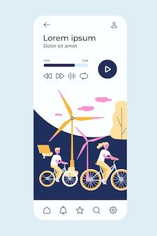 Люди катаются на велосипедах у ветряных мельниц и солнечной электростанции