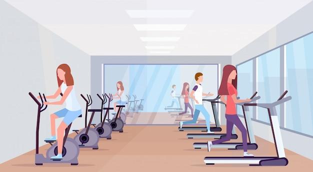 トレッドミルを実行し、静止した自転車に乗るスポーツ活動健康的なライフスタイルコンセプト男性女性グループモダンなジムインテリア全長水平を働く人々