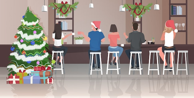 People in santa hats sitting on stools at cafe celebrating christmas
