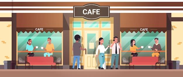 お茶を飲んでいる男性と女性がテーブルに座っている人々コーヒーブレークを持つモダンなストリートカフェの外観を持つレースの訪問者