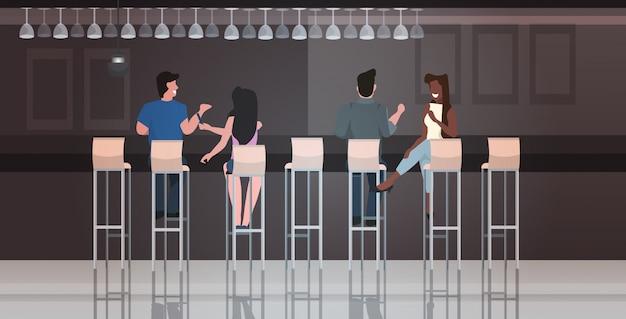 Люди сидят на табуретках в баре и обсуждают во время встречи