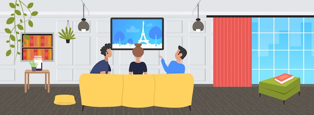 People sitting on sofa rear view friends watching famous landmarks tv travel show concept paris city silhouette on television modern living room interior  portrait horizontal