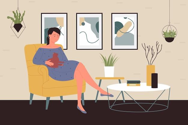 人々は家でペットと一緒に時間を過ごす幸せな女性は猫と一緒に快適なアームチェアに座っています