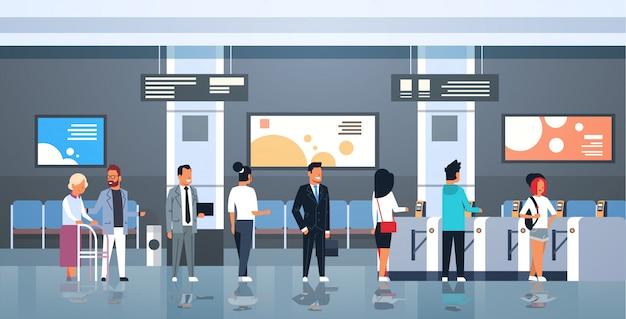 自動改札機の公共交通機関の駅の改札口の入口の男性の女性乗客が鉄道のプラットホームの地下鉄のパスで列の待ち行列に立っている人々