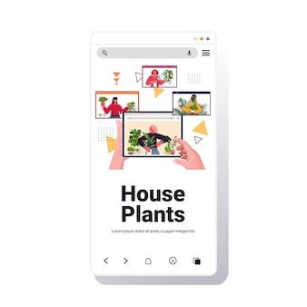 ハウスプラントの世話をしている人々は、ウェブブラウザウィンドウズスマートフォン画面ポートレートコピースペースでビデオ通話中に議論しているレースハウスキーパーを混合します