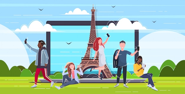 People taking selfie photo on cellphone camera mix  men women using smartphones paris abstract city famous construction silhouette on laptop screen  full length horizontal