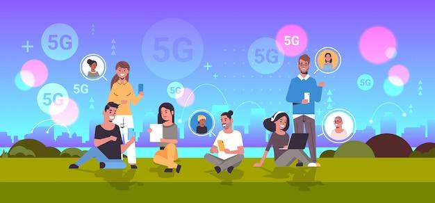 デジタルデバイスを使用している人々ソーシャルネットワーク通信5 gオンラインワイヤレスシステム接続概念ミックスレース男性女性夏の公園都市景観背景全長水平