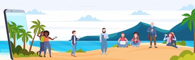 Люди, использующие гаджеты микс мужчины женщины отдых на тропическом острове море пляж летние каникулы цифровая зависимость концепция смартфон экран мобильное приложение полная длина горизонтальный