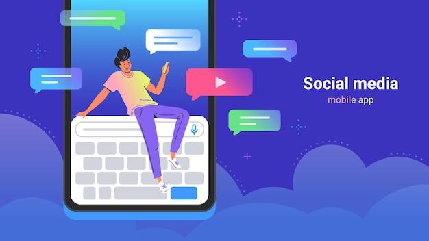 채팅, 비디오 공유 및 구독을 위해 소셜 미디어를 사용하는 사람들. 큰 디지털 키보드에 앉아 친구에게 문자 메시지를 보내기 위해 스마트폰 모바일 앱을 사용하는 젊은 남자의 개념 벡터 그림
