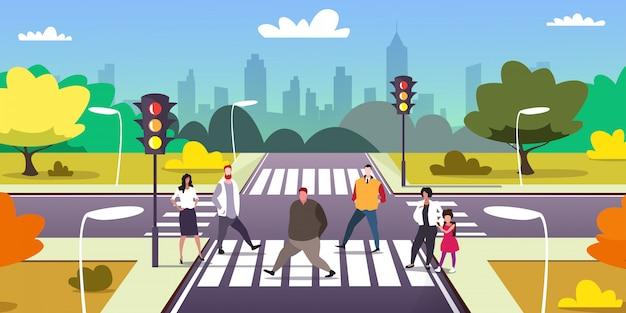 People walking on city street crosswalk urban traffic lights cityscape