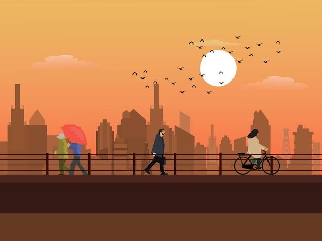 建物と夕日を背景にした高架道路を歩く人々