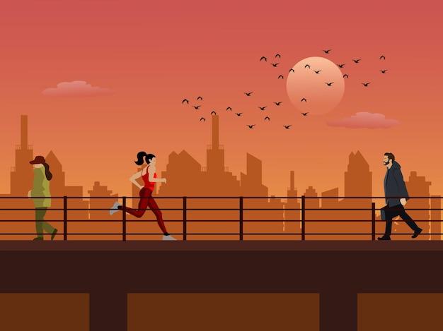 街と夕日を背景に高架を歩く人々