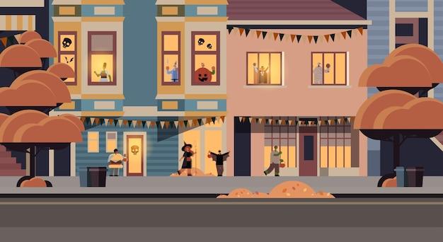 町のトリックを歩いて別のモンスターの衣装を着ている人は、ハッピーハロウィーンパーティーのお祝いのコンセプトの街の通りの建物の外観の街並みを扱います