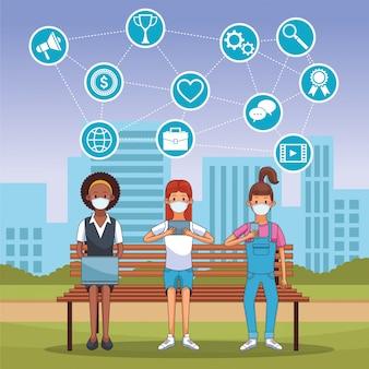 의료용 마스크와 스마트 폰 및 노트북을 착용 한 사람들은 연결 상태를 유지합니다.
