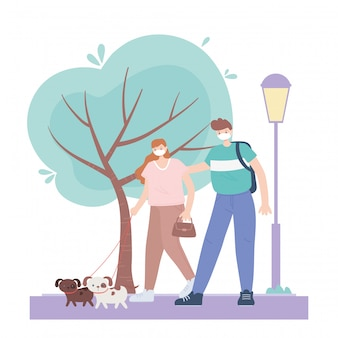 People with medical face mask, couple walking with dogs in the park