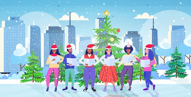 People with sheet books giving performance merry christmas happy new year holidays celebration concept  men women standing near fir tree modern cityscape
